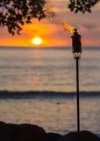 在日落的Tiki火炬 免版税库存图片