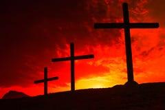 在日落红黄色天空的背景的三个十字架 耶稣在十字架上钉死的概念  免版税库存照片