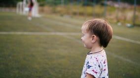 在日落背景的未认出的儿童游戏橄榄球  慢的行动 股票录像