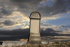 在日落背景的老墓碑 库存图片