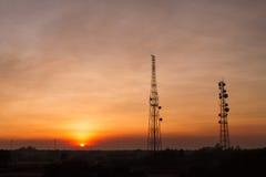 在日落背景的通讯台 图库摄影
