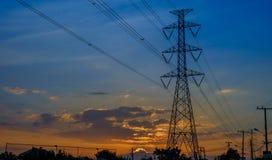 在日落背景的高压塔 免版税图库摄影