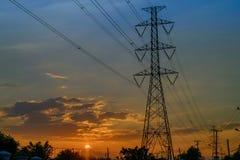 在日落背景的高压塔 库存图片