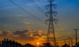 在日落背景的高压塔 免版税库存照片