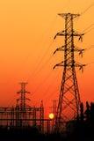 在日落背景的高压电柱子 库存图片