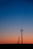 在日落蓝色红色桔子的电线 库存图片
