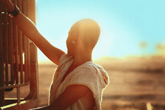 在日落风景的刮带头的女孩剪影 库存照片