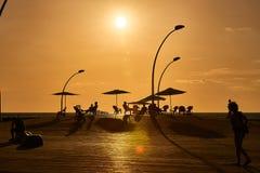 在日落,人们散步到特拉维夫口岸散步 免版税库存图片