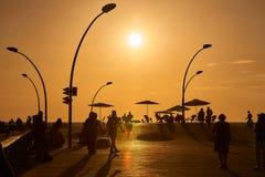 在日落,人们散步到特拉维夫口岸散步 免版税库存照片