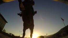 在日落,剪影车手的马跳跃的障碍 股票录像