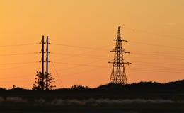 在日落,反对一个未来派风景的背景的日落的输电线 库存照片