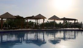 在日落,在死海,约旦的手段的背景的游泳池 免版税库存图片