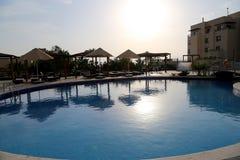 在日落,在死海,约旦的手段的背景的游泳池 库存照片