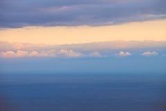 在日落,桃红色云彩的海洋水平的风景 库存照片