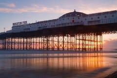 在日落,温暖的红色和橙色颜色的布赖顿码头 免版税库存图片