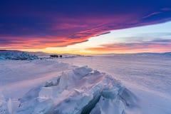 在日落,破裂的结冰的湖的冬天风景被盖雪在贝加尔湖在俄罗斯用美丽的日落天空 库存照片