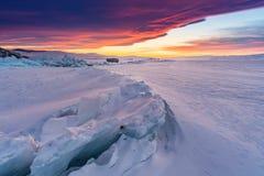 在日落,破裂的结冰的湖的冬天风景被盖雪在贝加尔湖在俄罗斯用美丽的日落天空 免版税图库摄影