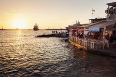 在日落,米科诺斯岛希腊的咖啡馆 图库摄影