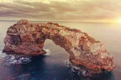 在日落,自然石曲拱的ES Pontas在Cala Santanyi, Mallor 免版税库存图片