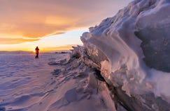 在日落,雪盖的湖破裂的结冰的冰的冬天风景在贝加尔湖,日落的俄罗斯 免版税库存图片