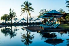 在日落, Gili Trawangan,龙目岛,印度尼西亚期间,在热带手段的游泳池附近使sunbeds靠岸与棕榈 免版税库存照片