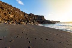 在日落, playa del Paso,兰萨罗特岛,西班牙的狂放的黑沙子海滩 库存照片