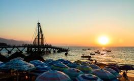 在日落-巴亚尔塔港,哈利斯科州,墨西哥的Los Muertos码头 免版税库存图片