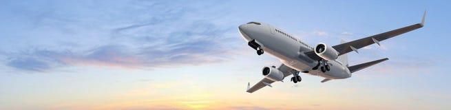 在日落-全景的现代乘客飞机飞行 图库摄影