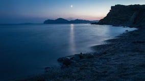在日落以后的有卵石花纹的沿海 库存图片