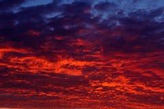 在日落以后的火热的云彩在海 免版税库存图片