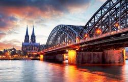 在日落-夜的科隆大教堂和Hohenzollern桥梁 免版税库存图片