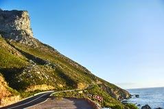 在日落Boland山复合体,西开普省的海边路 免版税库存图片