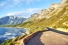 在日落Boland山复合体,西开普省的海边路 免版税库存照片