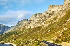 在日落Boland山复合体,西开普省的海边路 库存图片