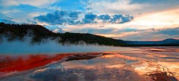 在日落cloudscape下的盛大多彩春天在中途喷泉水池在黄石国家公园在怀俄明 库存图片