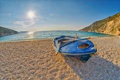 在日落Myrtos海滩的老被放弃的渔夫小船在Kefalonia,希腊 免版税库存照片