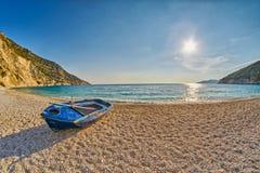 在日落Myrtos海滩的老被放弃的渔夫小船在Kefalonia,希腊 库存照片