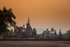 在日落Sukhothai历史公园, Mahathat寺庙,泰国的古老菩萨雕象 库存图片