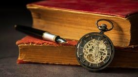 在旧书和笔旁边被安置的绞的怀表在书 库存图片