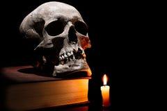 在旧书的人的头骨与在黑背景的灼烧的蜡烛 免版税库存照片