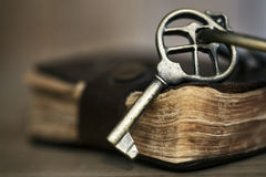 在旧书的古色古香的黄铜关键字 免版税库存图片