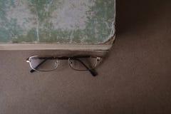 在旧书附近的玻璃与被撕毁的边缘和破旧的盖子 r r 库存图片