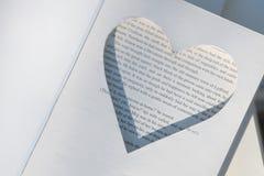 在旧书,以心脏的形式一个框架被删去 圆环的地方 婚礼概念 库存照片