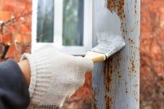 在旧布手套底涂反铁锈的手在建筑的钢杆 库存照片