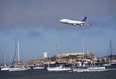 在旧金山湾之上的团结的航空公司飞机飞行 免版税库存图片