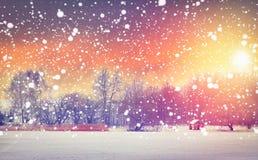 在早晨五颜六色的日出的冬天降雪 抽象空白背景圣诞节黑暗的装饰设计模式红色的星形 发光在明亮的太阳的雪花 Xmas和新年场面 图库摄影