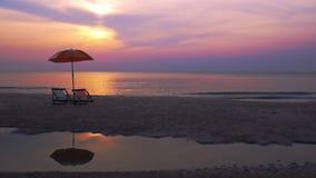 在早晨天空的日出在有椅子的在海滩的海和伞反射 股票录像