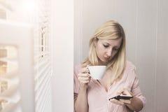 在早晨太阳和使用智能手机的女商人饮用的咖啡 库存照片