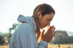 在早晨女孩被关闭她的眼睛,祈祷户外,手在信念的,灵性,宗教概念祷告概念折叠了 免版税库存照片
