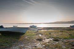 在早晨日出期间的渔船处于低潮中在出海口 免版税图库摄影